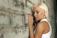 美丽的白肤金发的摆在的墙壁 库存照片