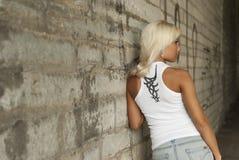 美丽的白肤金发的摆在的墙壁 免版税库存照片