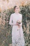 年轻美丽的白肤金发的有花束的新娘佩带的白色礼服在开花的草甸 精美女孩享受春天自然 免版税库存照片