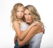 美丽的白肤金发的母亲和女儿互相拥抱 免版税库存照片