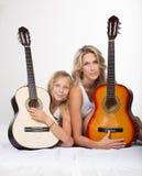 美丽的白肤金发的母亲和她的女儿有吉他的 库存图片