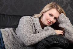 美丽的白肤金发的灰色编织毛线衣妇&# 免版税库存图片