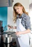 美丽的白肤金发的烹调妇女 免版税库存照片