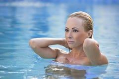 美丽的白肤金发的蓝色池游泳妇女 免版税库存照片