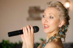 美丽的白肤金发的话筒妇女 免版税图库摄影