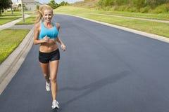 美丽的白肤金发的跑步的MP3播放器妇&#22899 免版税库存图片