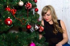 美丽的白肤金发的近的圣诞树 免版税库存照片