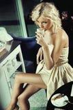 美丽的白肤金发的饮用的女孩 免版税库存图片