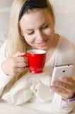 美丽的白肤金发的饮用的早晨咖啡和检查巧妙的电话 免版税库存照片