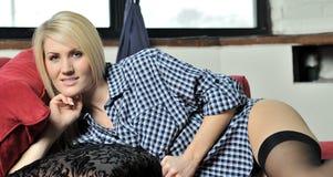 美丽的白肤金发的lounging的人s衬衣妇女 免版税库存照片