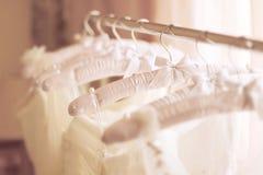 美丽的白色婚礼礼服由丝绸制成在挂衣架 免版税库存图片