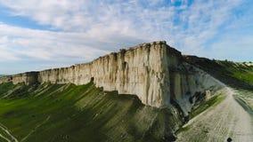美丽的白色岩石顶视图与绿草的在天空蔚蓝背景  ?? 白色峭壁全景与绿色的 股票视频