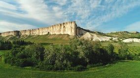 美丽的白色峭壁令人惊讶的看法在绿色草甸附近的有树和灌木的反对天空蔚蓝在夏天 ?? 影视素材