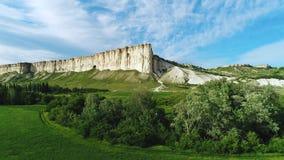 美丽的白色峭壁令人惊讶的看法在绿色草甸附近的有树和灌木的反对天空蔚蓝在夏天 ?? 股票录像