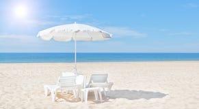 美丽的白色沙滩伞和太阳在海滩供住宿。 免版税图库摄影