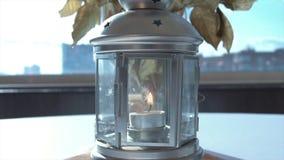 美丽的白色烛台特写镜头 英尺长度 在玻璃烛台的燃烧的蜡烛有在花瓶和瓶的花束的  免版税库存照片