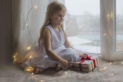 美丽的白色礼服的梦中情人有礼物的 库存照片