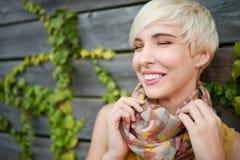 美丽的短发站立反对常春藤篱芭背景的白金白肤金发的妇女 免版税库存图片