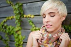 美丽的短发站立反对常春藤篱芭背景的白金白肤金发的妇女 免版税库存照片