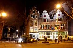 美丽的矮小的传统房子在阿姆斯特丹在夜 免版税库存照片