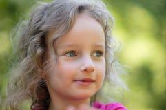 美丽的矮小的卷曲白肤金发的女孩,有愉快的乐趣快乐的微笑的面孔,大蓝眼睛,长的睫毛 画象 免版税库存图片