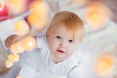 美丽的矮小的婴孩庆祝圣诞节 新年` s假日 逗人喜爱的礼服的甜女婴获得乐趣在欢乐 免版税库存图片