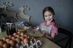 美丽的矮小的微笑的女孩烹调从鸡蛋的饼 免版税库存照片