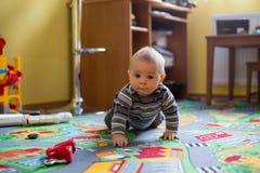 美丽的矮小的男婴、小孩微笑对照相机的,动物和恐龙在他,室内射击附近 免版税库存照片