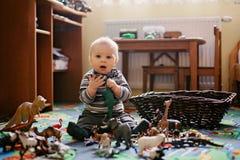 美丽的矮小的男婴、小孩微笑对照相机的,动物和恐龙在他,室内射击附近 库存照片
