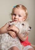 美丽的矮小的白肤金发的女孩和狗 免版税库存照片