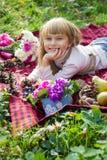 美丽的矮小的年轻婴孩在红色格子花呢披肩说谎 微笑与明亮的花的可爱的孩子 免版税图库摄影