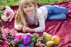 美丽的矮小的年轻婴孩在红色格子花呢披肩说谎 微笑与明亮的花的可爱的孩子 库存图片