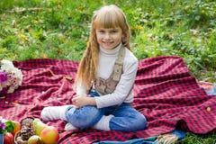 美丽的矮小的年轻婴孩坐红色格子花呢披肩 微笑与明亮的花的可爱的孩子 免版税库存图片