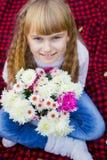 美丽的矮小的年轻婴孩坐红色格子花呢披肩 微笑与明亮的花的可爱的孩子 库存照片