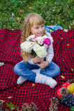 美丽的矮小的年轻婴孩坐红色格子花呢披肩 微笑与明亮的花的可爱的孩子 免版税库存照片