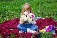 美丽的矮小的年轻婴孩坐红色格子花呢披肩 微笑与明亮的花的可爱的孩子 免版税图库摄影