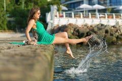 美丽的码头坐的妇女 免版税图库摄影