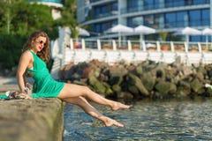 美丽的码头坐的妇女 免版税库存照片