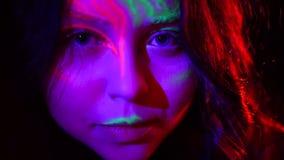 美丽的确信的女孩特写镜头画象有去阶段霓虹的构成的做表现 逗人喜爱的女孩张开她的眼睛 股票录像