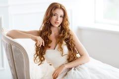 美丽的礼服坐的基于的新娘沙发户内 库存图片