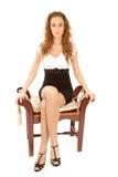美丽的礼服无背长椅坐的妇女 免版税库存图片
