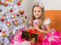 美丽的礼服的七年女孩在他们的手上坐与一件礼物 库存图片