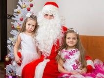 美丽的礼服的两个女孩拥抱圣诞老人坐长沙发,他们中的一个一点生气 免版税库存照片
