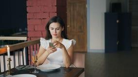 美丽的礼服的可爱的年轻女人在坐在单独桌和使用上的餐馆等待她的男朋友 股票视频