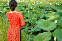 美丽的礼服的女孩在莲花湖 免版税库存图片