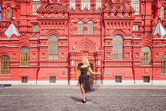 美丽的礼服的微笑的女孩在红场 免版税库存照片