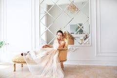 美丽的礼服的新娘坐户内沙发在白色演播室内部在家喜欢 时髦婚礼样式 免版税库存图片