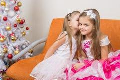美丽的礼服的耳语两个的女孩坐长沙发 免版税库存照片