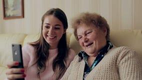 美丽的祖母和女儿做着selfie并且微笑着,当在家时坐长沙发 股票视频