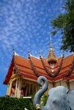 美丽的神圣的红色著名佛教寺庙屋顶和金黄尖顶主要大厅有蓝天和白色云彩背景的 图库摄影